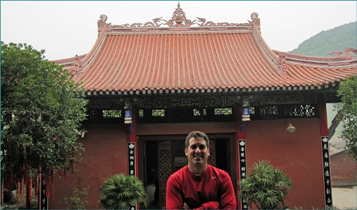 John Gunter in front of a Buddhist temple in Asia.